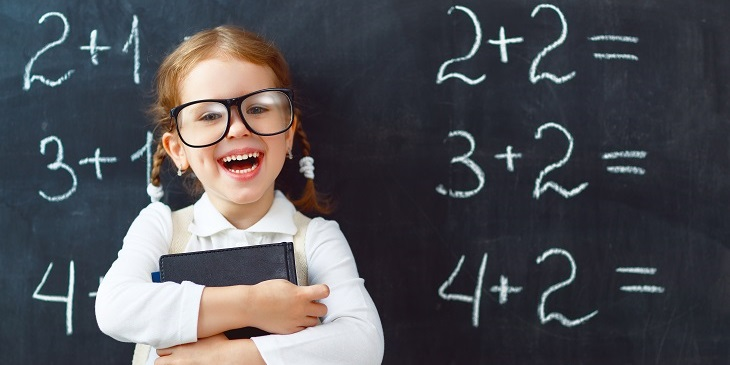 kid works out answers on blackboard